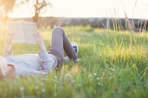 Guy reading in a field