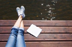 girl reading out by the lake during summer break