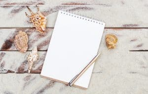 Blank notepad with seashells on the sand, which scattered on wooden planks. Vacation and travel concept.